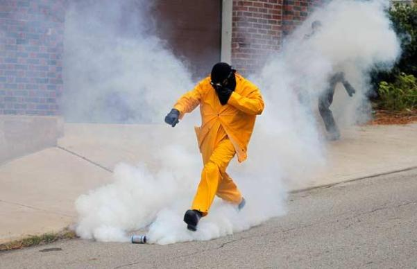 A demonstrator kicks a tear gas canister fired by police